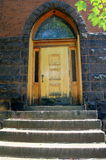 Old wood door in stone and brick church. Old wood door under archway of stone and brick church Royalty Free Stock Image