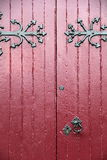 Old wood doors in shades of maroon, with heavy black hardware Royalty Free Stock Photography