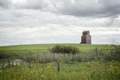Old wood elevator in the distance sitting in a green meadow Royalty Free Stock Photos