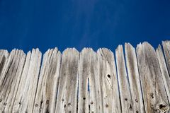 Old wood fence and bright blue sky. With room for text Royalty Free Stock Photos