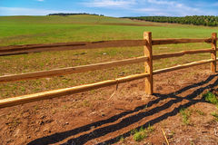 Old wood fence with a green field Stock Photo