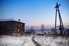Old wood frame house in the snow at sunset royalty free stock image