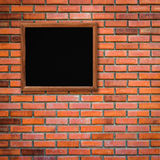 Old wood frame on red brick wall background Stock Photo