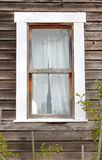 Old Wood Frame Window. Vertical view of an old wood frame window with curtains Royalty Free Stock Image
