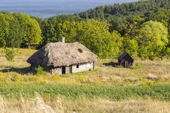 Old wood house with thatched roof in summer Sunny day, ancient building Stock Image