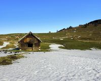 Old wood hut in a hilly landscape with snow over the grass stock images