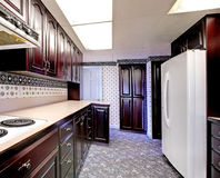 Old wood narrow kitchen with carpet and curtains. Stock Photography