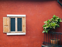Old wood open window. On red wall and tree Royalty Free Stock Photography