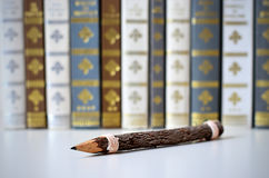 Old wood pencil with a background of old books. Royalty Free Stock Image