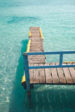 Old wood pier on a turquoise water sea. Stock Images