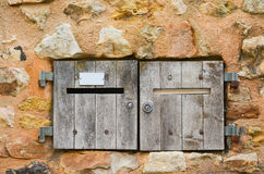Old wood postbox. Old wood postbox mounted in a stone wall stock photo