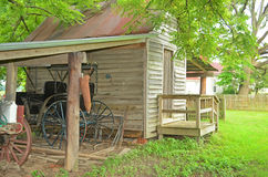 Old Wood Shed Antique Horse Carriage. Small old wooden shed with shelter covering a antique horse carriage with wooden fencing and trees in the background Stock Image