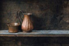 Old wood shelf. Copper jug and bowl on wood shelf royalty free stock photos