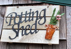 Old wood sign that any gardener would love. Old wood sign with metal words that read 'potting shed' and embellishment of pot with flowers inside Stock Photos