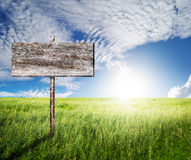 Old Wood sign with slope grass and blue sky Royalty Free Stock Images
