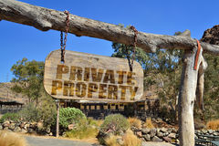 Old wood signboard with text `private property `. Hanging on a branch Royalty Free Stock Photo