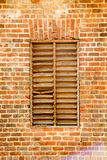 Old Wood Slat Window in Brick Wall Stock Photography