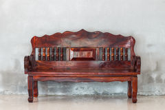 Old wood sofa chair on grunge wall background Stock Photography