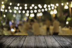 Old wood table with lighting bokeh blurred background. In outdoors restaurant Stock Photography