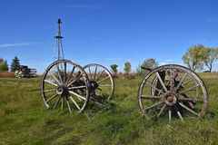 Old wood wagon wheels. Old wagon wheel with wood hub and spokes located in a meadow near the base of an old wind mill Stock Photography