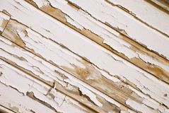 Old Wood Wall With Cracked White Paint on Angle. A very old wooden slat wall with severly distressed and cracked paint Stock Photos