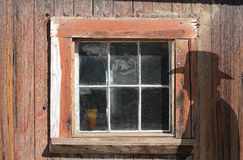 Old wood window and a cowboy silhouette. Royalty Free Stock Image