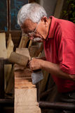 Old woodcarver working with mallet Royalty Free Stock Photos