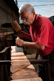 Old woodcarver working with mallet Royalty Free Stock Photography