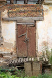 Old wooden abandoned door and brick wall. close up Stock Image