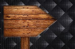 Old wooden arrows road sign  on black background Stock Images