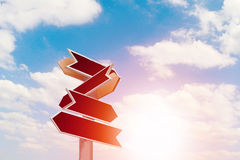 Old wooden arrows road sign on sky Stock Image