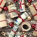 Old wooden background, American money, gifts and Christmas items. Top view. Different values. Effect snowflakes.  stock photography