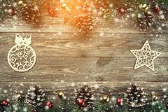 Old wooden background with fir branches adorned with cones. Space for text. Christmas card. Top view. Xmas holiday items. Effect. Of snow and light stock image