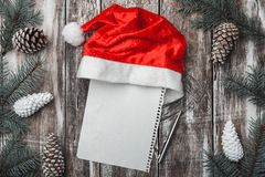 Old wooden background. Fir branches, cones. Christmas Fellowship, New Year and Xmas. Letter with message space for Santa. Holiday card. Santa`s Cap. Xmas and Stock Photo