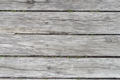 Old wooden background. Of several faded oak boards with wide slits and grass, a front view Stock Photography