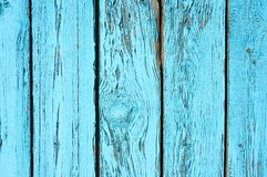 Old wooden background painted with blue paint paint with a texture of cracks and scratches. stock image