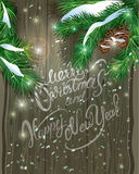 Old Wooden background with painted holiday typography, Christmas. Fir tree branches  and snow. Merry Christmas and Happy New Year calligraphy Stock Images