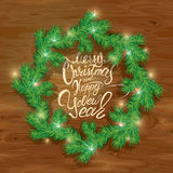 Old Wooden background with painted holiday typography, Frame of. Christmas fir tree branches  in circle shape. Merry Christmas and Happy New Year calligraphy Stock Images