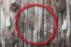 Old wooden background. Pine cones. Red decorative circle. Space for message Xmas, Christmas and New Year. Greeting card. Royalty Free Stock Photo