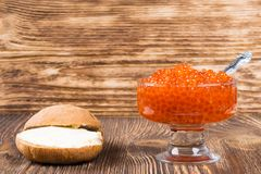 Old wooden background with a plate of red caviar, place for inscription royalty free stock image