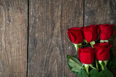 Old wooden background with red roses copy space. Top view Royalty Free Stock Photography
