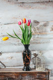Old wooden background with tulips in vase and candlestick Stock Image