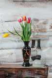Old wooden background with tulips in vase and kerosene lamp Stock Photography