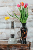 Old wooden background with tulips in vase and kerosene lamp Stock Images