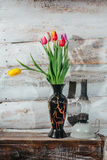 Old wooden background with tulips in vase and kerosene lamp Royalty Free Stock Photos