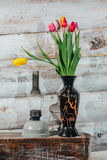 Old wooden background with tulips in vase and kerosene lamp Stock Photo