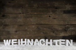 Old wooden background with white german letters for Christmas. Stock Photos