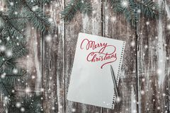 Old wooden background with white sheet on it with Merry Christmas message. Space for a congratulatory message. Old wooden background with white sheet on it with Stock Images