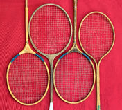 Old wooden badminton rackets on red background.  Royalty Free Stock Photos