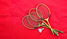 Old wooden badminton rackets and shuttlecock on red background.  Stock Photo